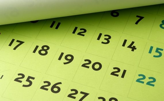 A page opened to a large format calendar with squares with numbers up to 28.