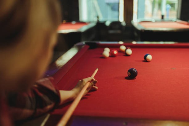over shoulder view of a person aiming to hit a ball on a red 8 ball table
