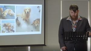 A young man with a beard, walking cane, hawaiian style shirt with a vintage car print and a suit jacket stands at a lectern. A screen behind him shows a photo of 3 pet dogs and trays of freshly cooked biscuits