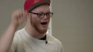 A man with a red beard, white t-shirt red flat brimmed cap and glases is speaking, with his fist waving in the air in an affirming position