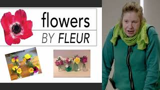 "a woman wearing a green winter jumper and scarf and holding a walking frame is presenting next to a screen displaying text ""flowers by Fleur"" and photos of flower arrangements."