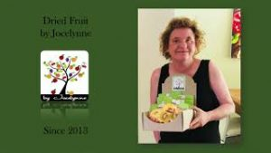 A green background presentation screen with logo of an illustrated tree with coloured leaves. Photo on the right of a woman in a black sleveless top holding a box of packaged dried fruit. She has chin length curly dark blonde hair and is smiling at the camera.