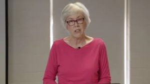 A woman with a bright pink long sleeved knit top and dark pink glasses is standing and speaking. She has light grey chin length hair.