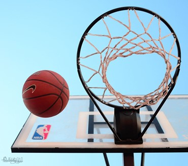 View from directly under a basketball hoop, with a basketball in the air next to it