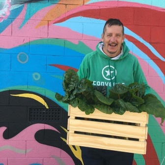 A tall man in a green hoodie is smiling and holding a large wooden crate filled with green leafy vegetables. He is standing in front of a brightly painted wall mural