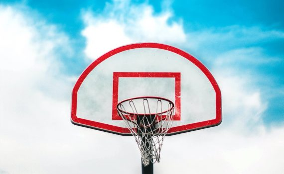 Reb and white basketball backboard with black basketball ring. Blue skies with white clouds can bee seen behind backboard.